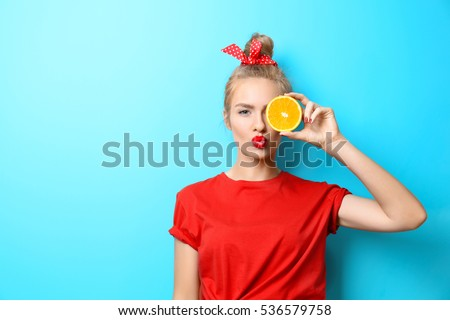 Young beautiful woman with orange on blue background