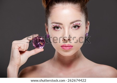 Young beautiful woman with perfect makeup, drawing bows, admiring the gem.