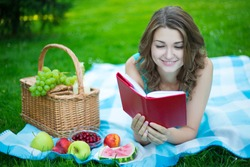 young beautiful woman with picnic basket and fruits reading book in summer park