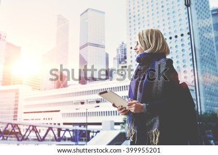 Young beautiful woman with portable touch pad in hands is enjoying view of New York business center outside the window background with copy space for advertising text message or promotional content stock photo