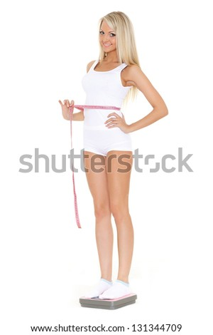 Young beautiful woman with scale and measuring tape on a white background.  Concept of healthy lifestyle.