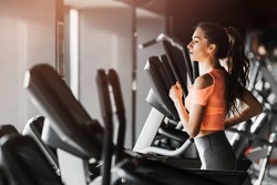 Young beautiful woman with slim sport figure running on treadmill in modern light gym. Place for text. Healthy and sporty lifestyle concept. Side view.