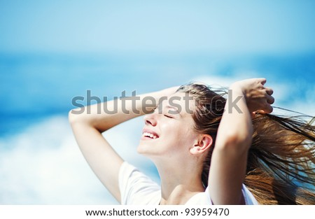 Young beautiful woman with streaming hair in front of the ocean