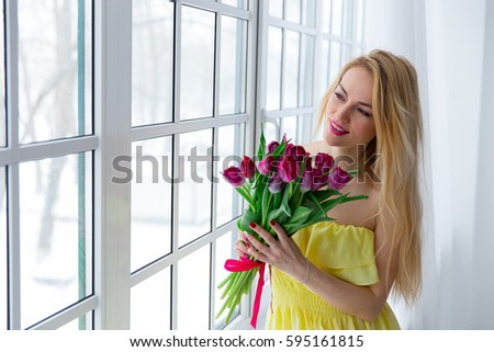 Young beautiful woman with tulip bunch in yellow dress looks at window. 8 march international womens day. #595161815