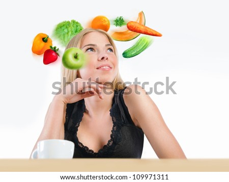 Young beautiful woman with vegetables, berries and fruits flying around her head. Healthy food and lifestyle concept