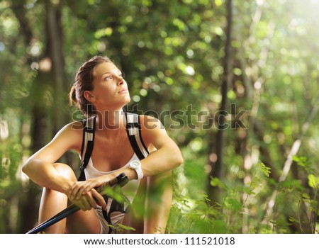 Young beautiful woman with walking sticks in a forest, having a break