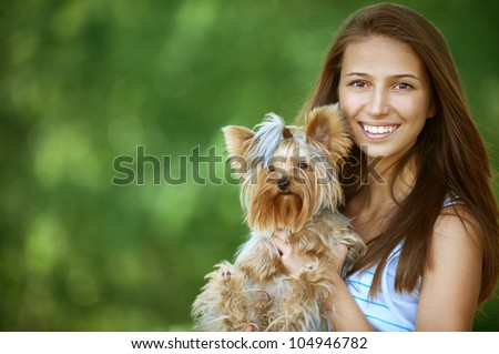 Young beautiful woman with Yorkshire Terrier, against green of summer park.