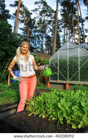Young beautiful woman working in her garden watering plants - stock photo