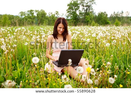 Young beautiful woman working with laptop in a spring blooming meadow