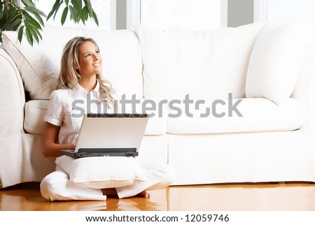 Young beautiful woman working with laptop  in the new  comfortable apartment - stock photo