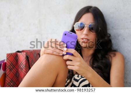 Young beautiful woman writing a sms message on phone