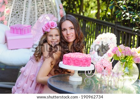 Young beautiful women and her daughter celebrate birthday with a cake
