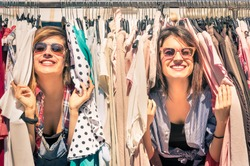 Young beautiful women at weekly cloth market - Best friends sharing free time having fun and shopping in old town on sunny day - Girlfriends enjoying everyday life moments - Looking at camera view