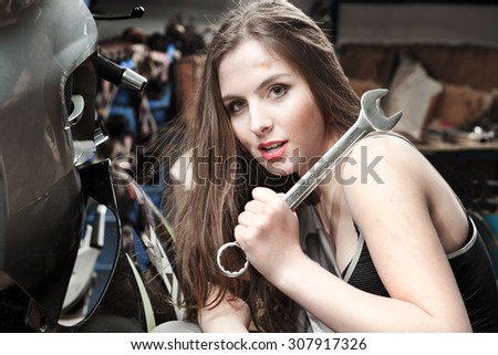 Young Beautiful Women car mechanic holding in his hand on the shoulder of a large wrench and ironically looking at the camera #307917326