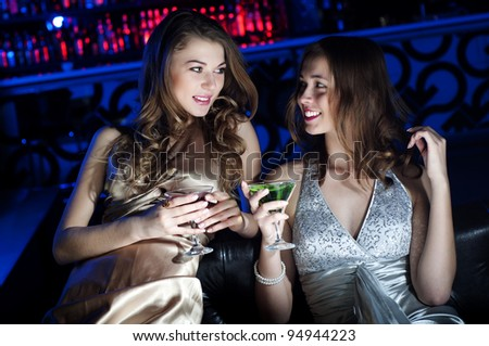 Young beautiful women, have a rest on a sofa and drink beverages