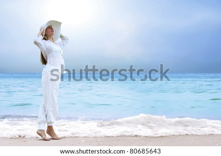 Young beautiful women in the white on the beach