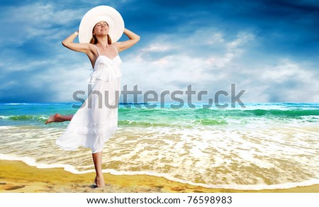 Young beautiful women in the white with pareo on the sunny tropical beach