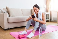 Young beautiful women resting and refreshment after exercising workout and using smart phone, checking social media on her phone and resting from exercises