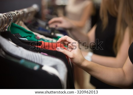 Shutterstock Young beautiful women shopping in fashion mall, choosing new clothes, looking through hangers with different casual colorful garments on hangers, close up of hands