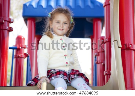 Young beautiful 3 years old girl playing in the children's park