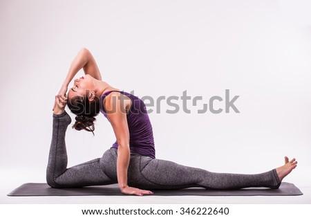 young beautiful yoga woman posing on a studio background Stock fotó ©