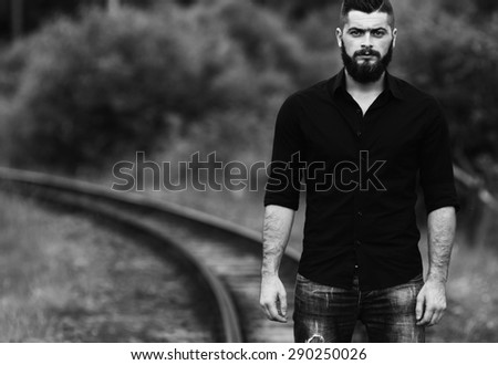 young beautiful young man standing on a railway line black and white photography