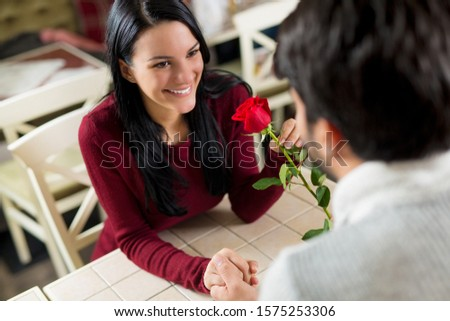 Young beautiful young woman being given a red rose