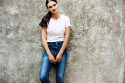 young beautifull woman wearing white t-shirt and denim jeans is posing against the grey street wall