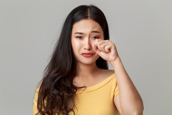 Young beauty Asian woman crying, sad emational, hand wiping tears on her face, studio headshot isolated on white background.