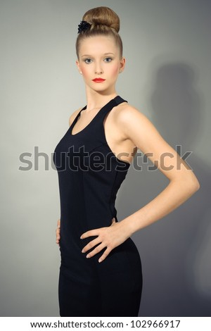 Young beauty fashion model wearing black evening dress and posing at camera in studio
