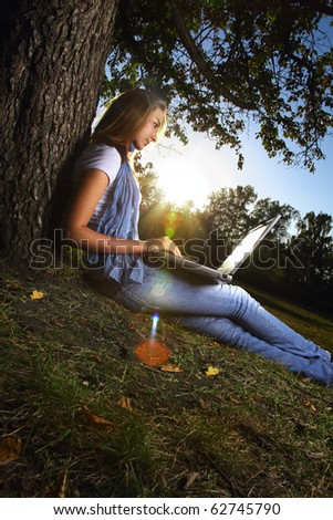 young beauty girl with laptop in park, photo with artistic lens flare effect