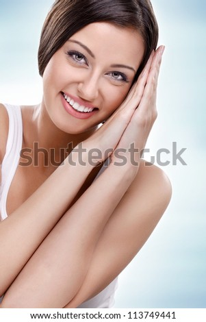 Young beauty - smiling woman, isolated on blue background