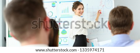 Young beauty teacher woman in class room workgroup seminar board with chart coaching background. Lecturer applicants retraining financial statistics management enterprise etiquette corporate spirit