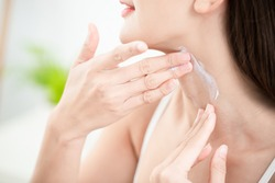young beauty woman applying cream or sunscreen on her neck