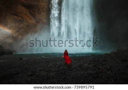 Young beauty woman over nature waterfall background in Iceland. Mysterious girl in a long red dress watch Skogafoss waterfall in the Iceland. #739895791