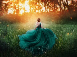 young beauty woman queen red hair runs dark mysterious forest lady long elegant royal emerald dress flying train spring tree grass sunset art photo bare open back no face turned away clothes costume