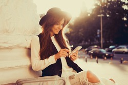 young beauty woman travel, using smartphone, happy face, hipster girl, sunset time, touch smartphone, bag, hat, backpack, phone, call,