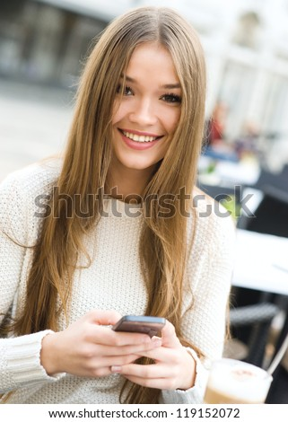 Young beauty woman writing message on cell phone in a street cafe. Looking at camera