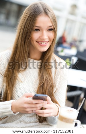 Young beauty woman writing message on cell phone in a street cafe. Looking away