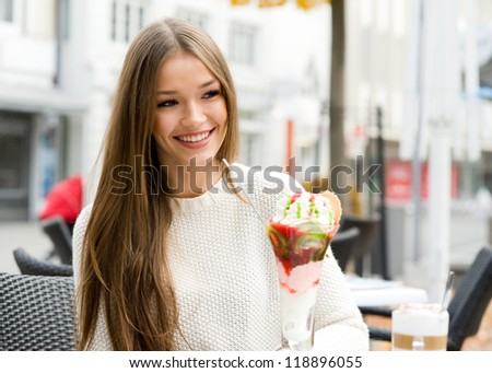 Young beauty women sitting in a street cafe with ice cream