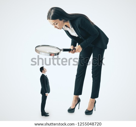 Young bent businesswoman looking at subordinate through binocular glass on white background. Talent search and hr concept
