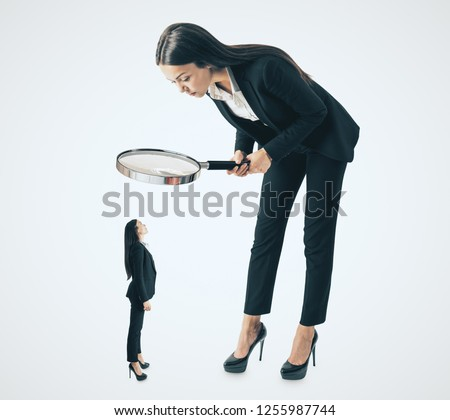 Young bent businesswoman looking at subordinate through binocular glass on white background. Talent search and hiring concept