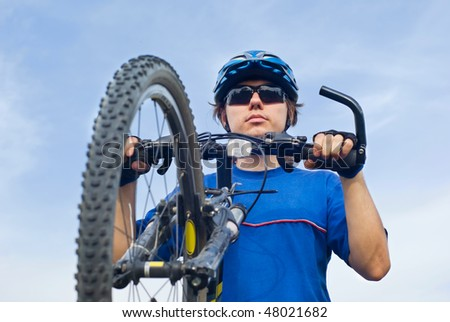 young bicyclist in helmet on a blue sky background