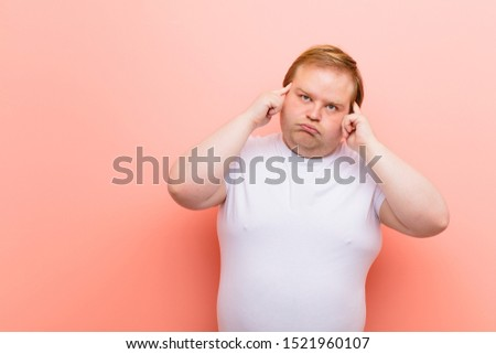 young big size man feeling confused or doubting, concentrating on an idea, thinking hard, looking to copy space on side against pink wall