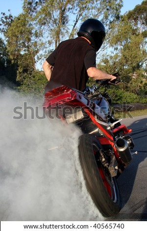 Young biker doing a doughnut on his motorcycle and making lots of smoke