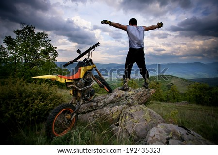 young biker on top of high spot feel free, sunset hdr landscape