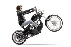 Young biker riding a custom motorbike on one wheel isolated on white background