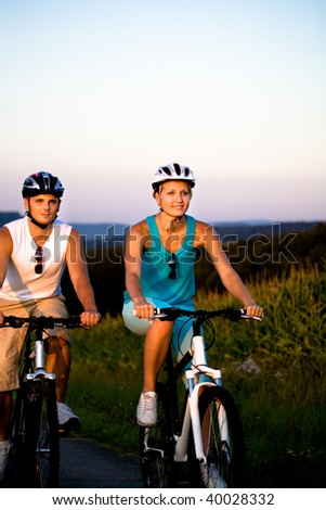young bikibg couple on countryside road