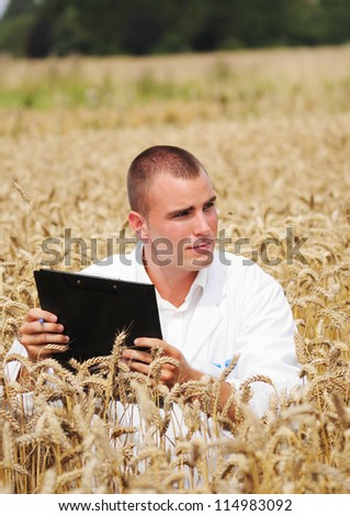 Young biologist in the field takes notes about scientific experiment in the wheat field