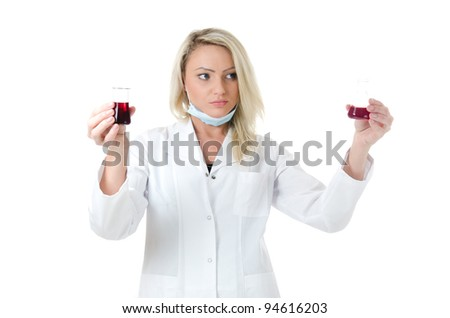 Young biology student in white coat holding a cylinder with strange orange liquid